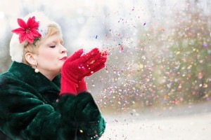 woman blowing glitter during holiday season