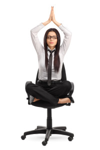 Vertical shot of a young businesswoman practicing yoga seated on an office chair isolated on white background