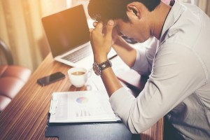man looking down stressed at work